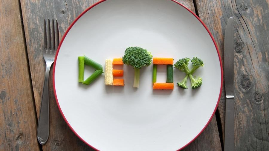 Dinning fork, plate and a knife. The plate has written text saying detox in the middle by using different veggies as carrots, broccoli and spring onion