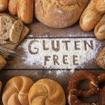 Top view of different types and shapes of gluten free breads on a wood background, forming almost a cirle, and text in the middle written apparently with finger on a white flour that says gluten free