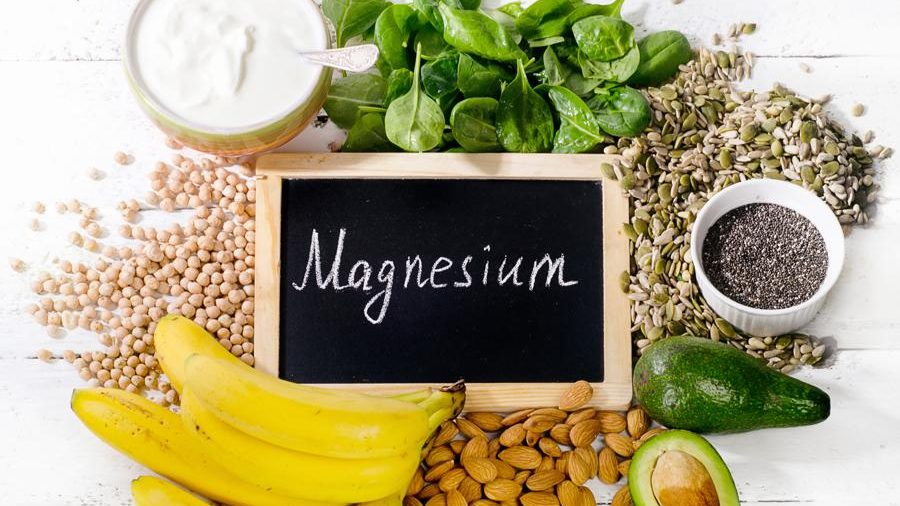 Top view of Magnesium rich foods spread together on a white table including: bananas, almonds, avocados, milk, green leafy veggies