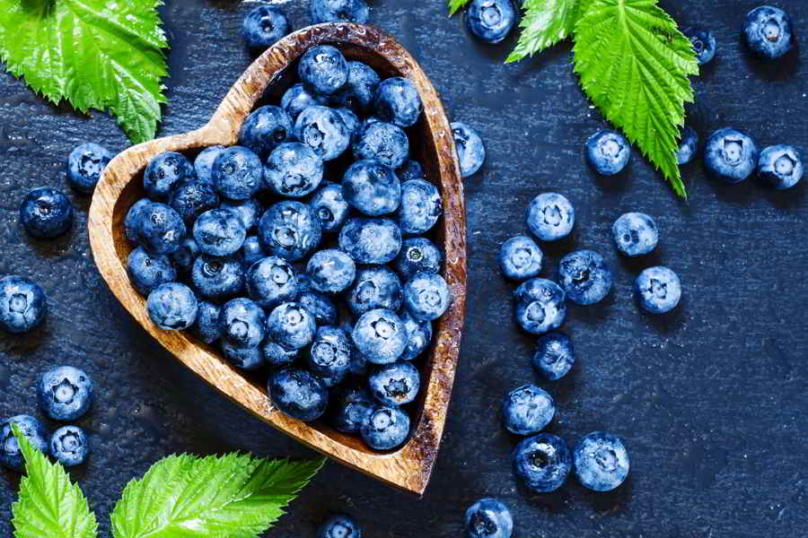 Fresh blueberries with water droplets and green leaves in a wooden bowl