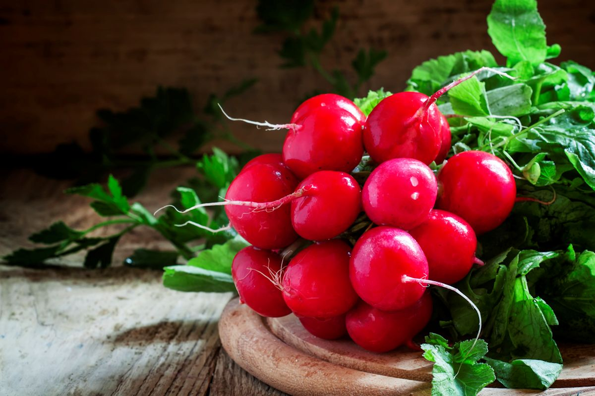 Bunch of red radishes on a cutting board