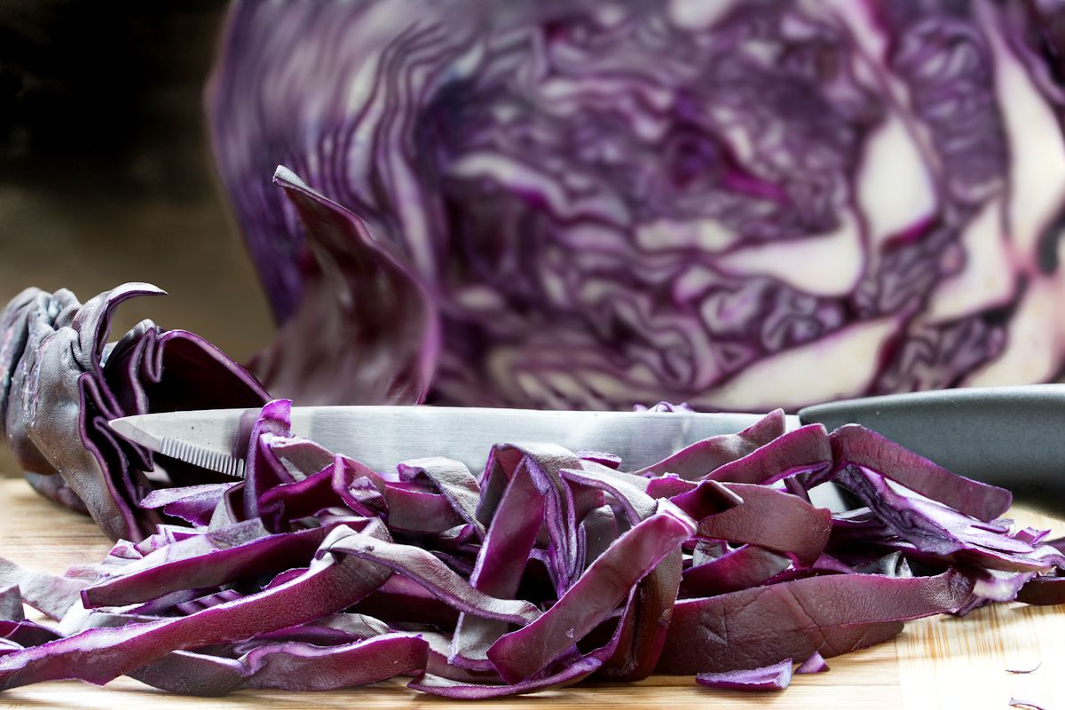Cutting red cabbage into fine strips on a wooden board