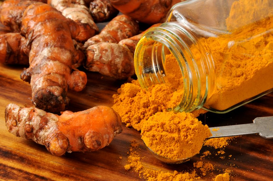 fresh turmeric and spice in a jar and spoon