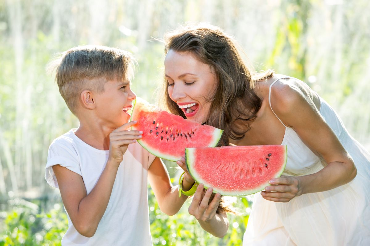 Happy smiling family eating watermelon on a sunny summer day