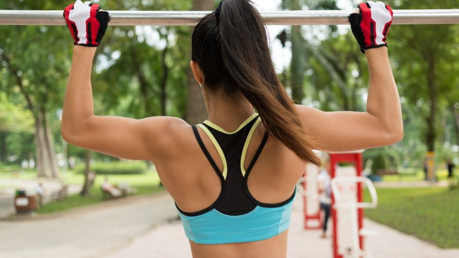 Woman doing chin-ups with gloves